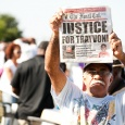 An older gentlemen holds a newspaper as a sign - Justice for Trayvon